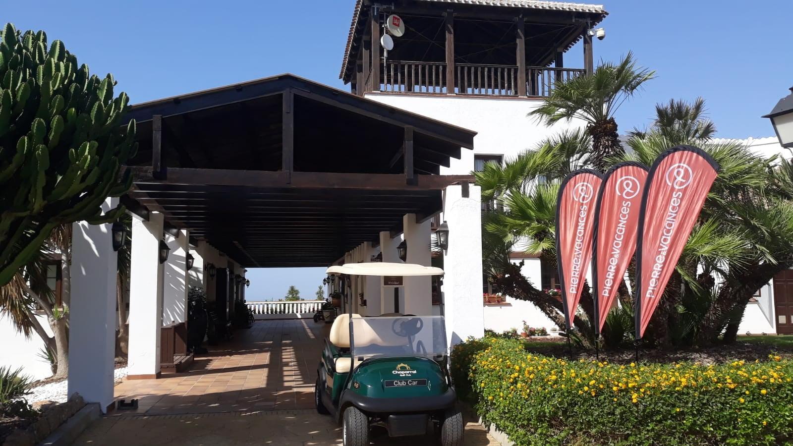 carrito de golf frente a un hotel y pancartas de Pierre et Vacances
